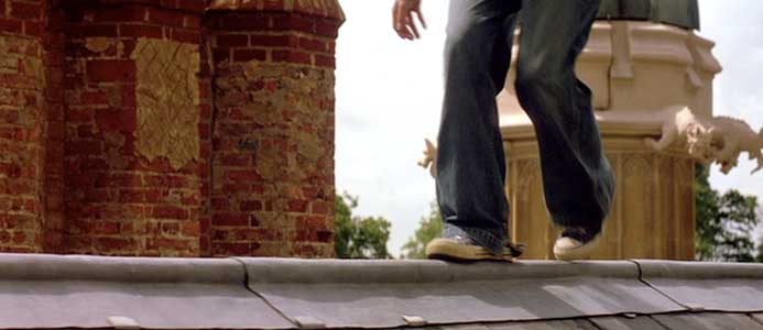 The camera focuses on Cody's chucks, as he climbs on the roof of a mansion