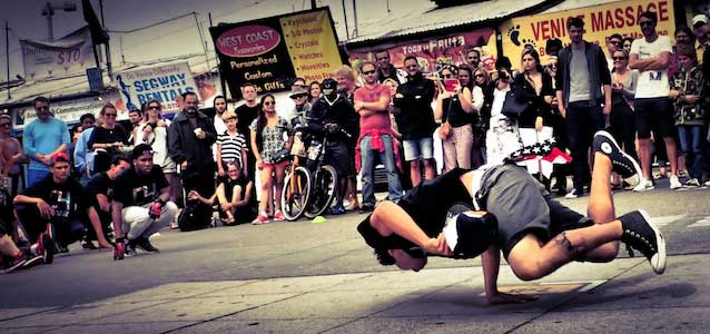 A breakdancer wears chucks performing in front of a crowd at Venice Beach