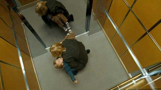 Carol carries the exhausted Oliver up a high rise elevator