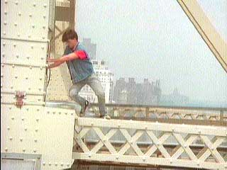 George starts to climb to the edge of the bridge's metalwork.