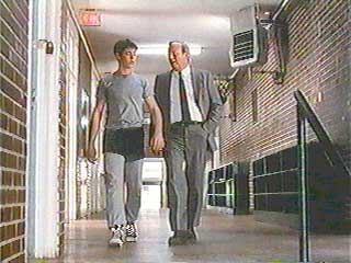 The school principal brings Billy to his locker for a drug search