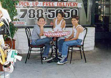 Louie is seated in front of his family's pizza parlor with Joey and J.J.